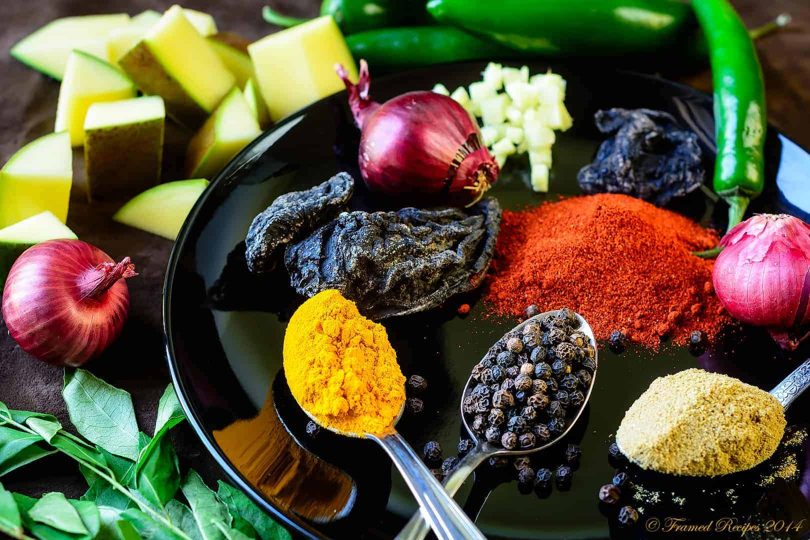 spices for Kerala style fish curry - mango, green chillies, whole black pepper, red chilli powder, coriander powder, curry leaves, shallots, tamarind and turmeric.