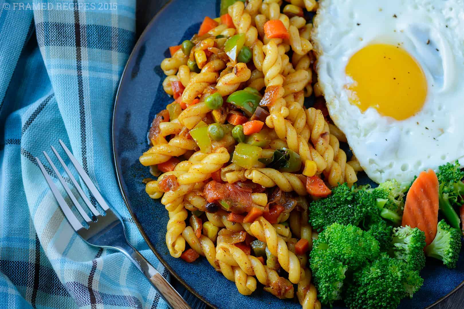 Indian masala pasta served with over-easy eggs and steamed broccoli and carrots.