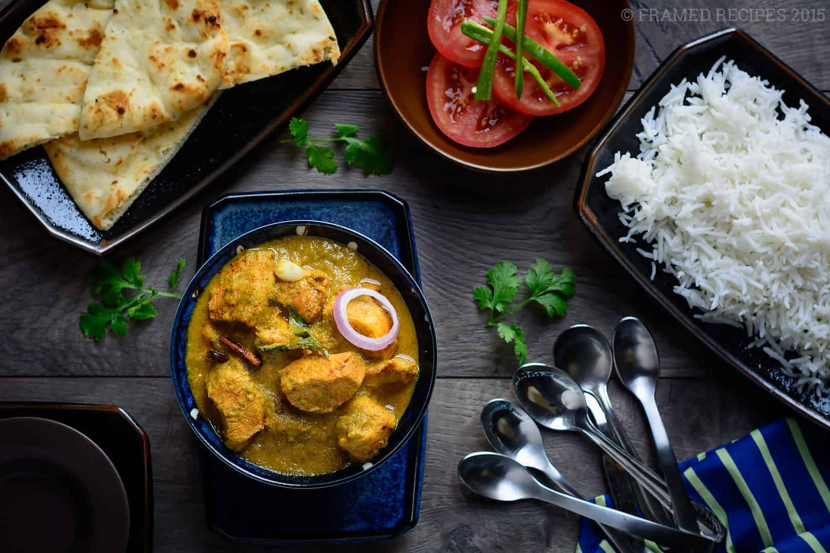 Cilantro Chicken Curry served with rice, naan and tomato slices with cutlery and serving plates on the side.