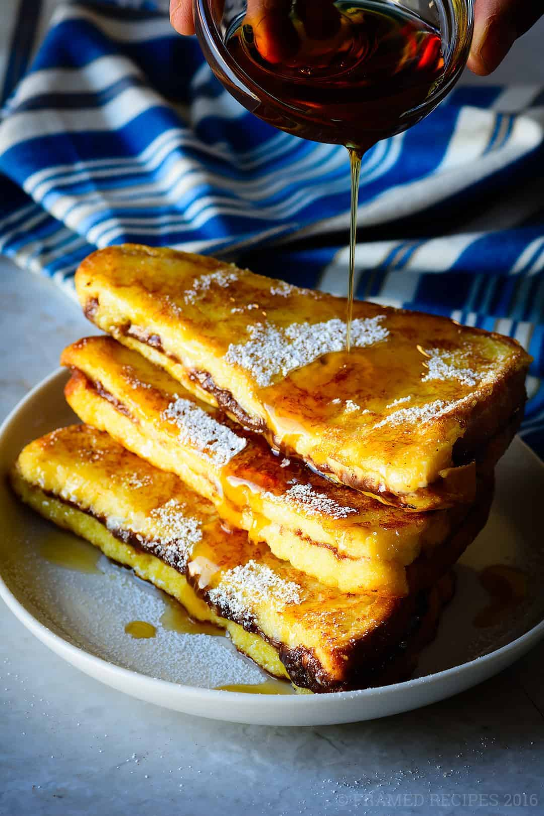 maple syrup drizzled over Nutella Cream Cheese French Toast.