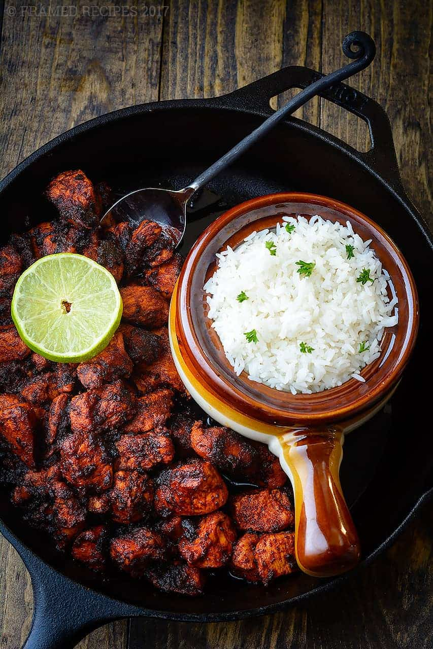Chicken Ghee Roast in a large cast-iron skillet with rice and lemon slice for garnish.
