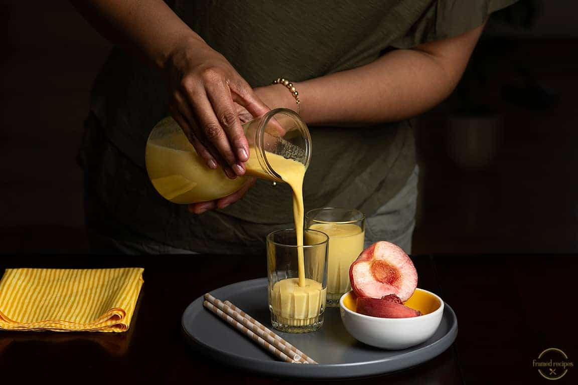 lady pouring peach turmeric smoothie to a serving glass.