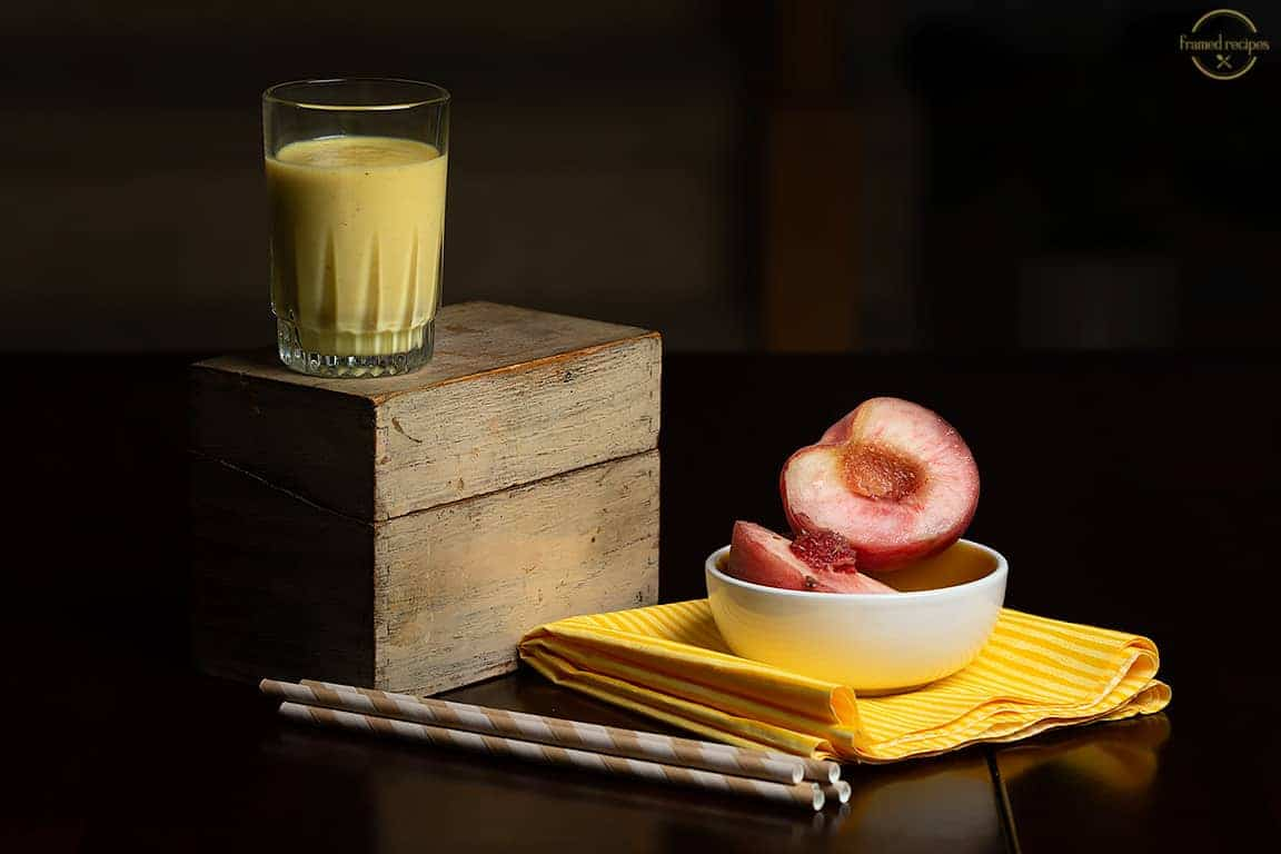peach turmeric smoothie shown with fresh peaches.