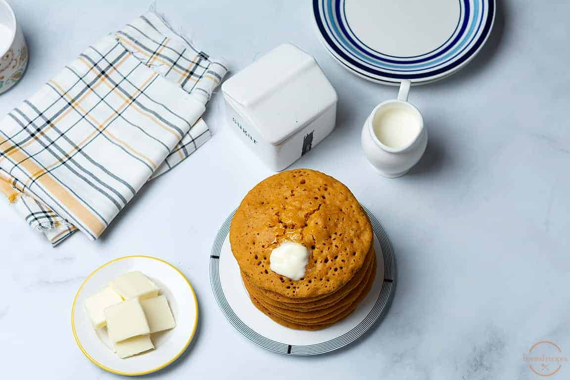 stack of pumpkin pancakes served with butter.