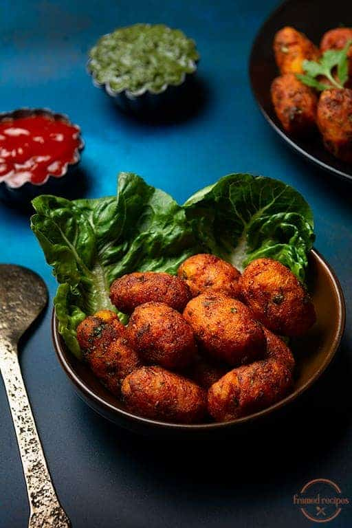 Cauliflower tots in a brown bowl with lettuce leaf as garnish with ketchup and mint chutney