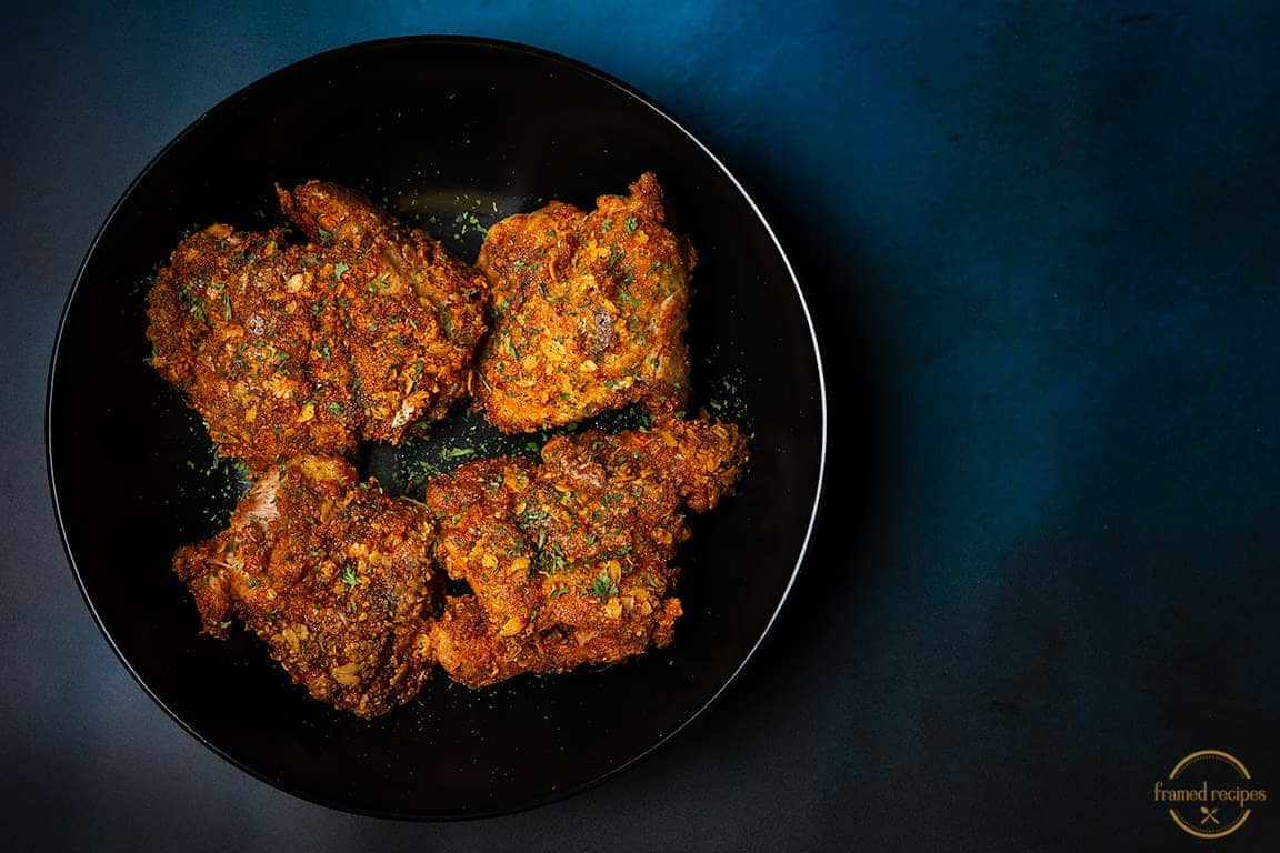 Spicy_Oats_Crusted_Chicken_Thighs_in_a_black_plate_horizontal_image
