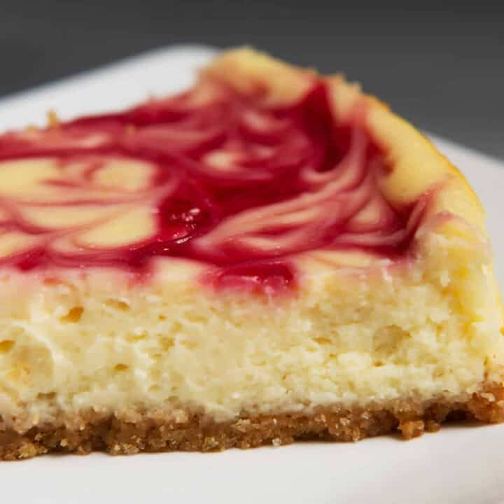 closeup shot of cheesecake slice with graham cracker crust, cheesecake filling and raspberry swirl