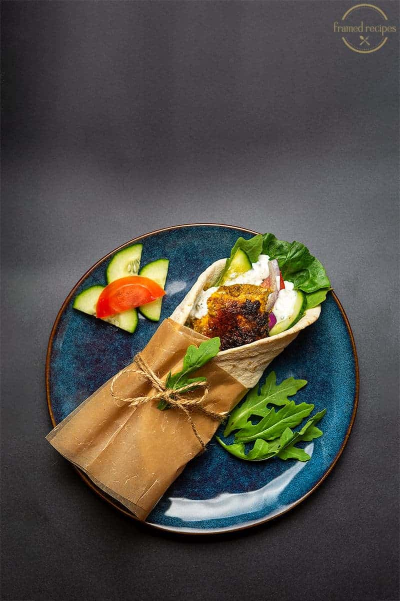 green chutney chicken wrap on a blue plate with sliced cucumbers, tomatoes on the side.
