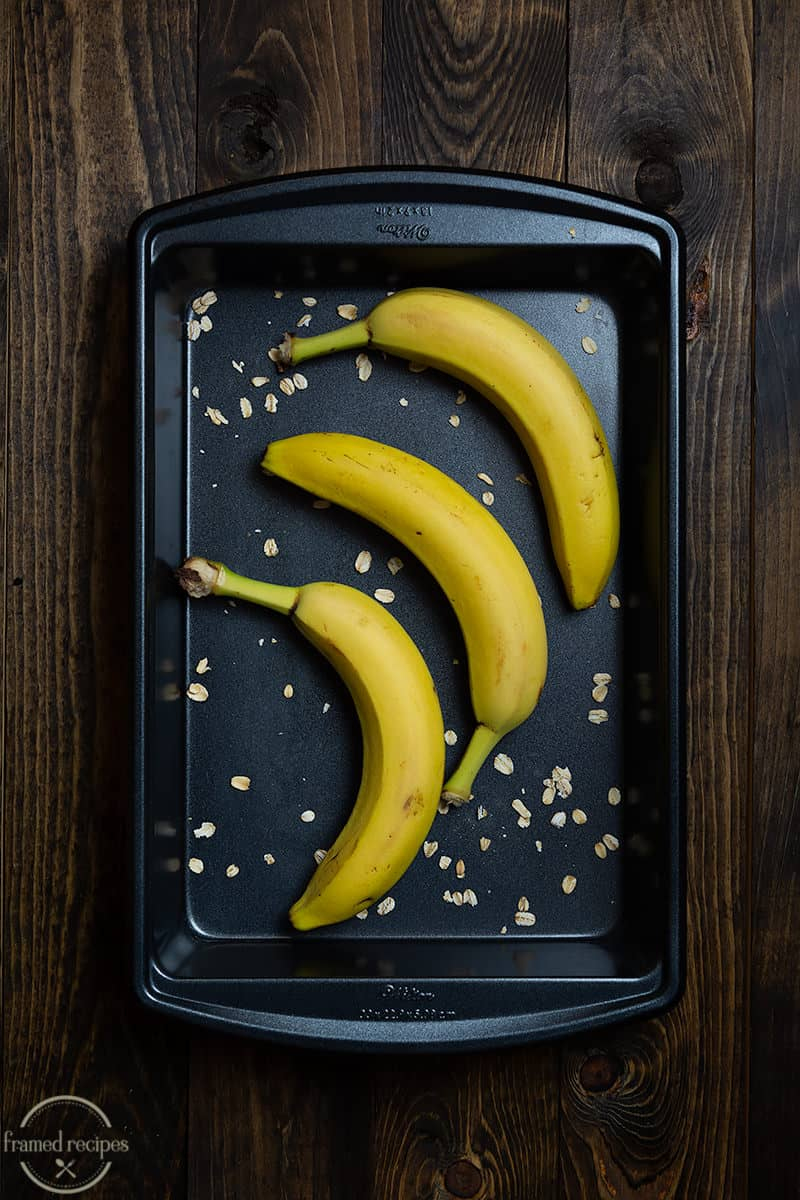 ripe bananas placed in a baking tray with oats sprinkled around.