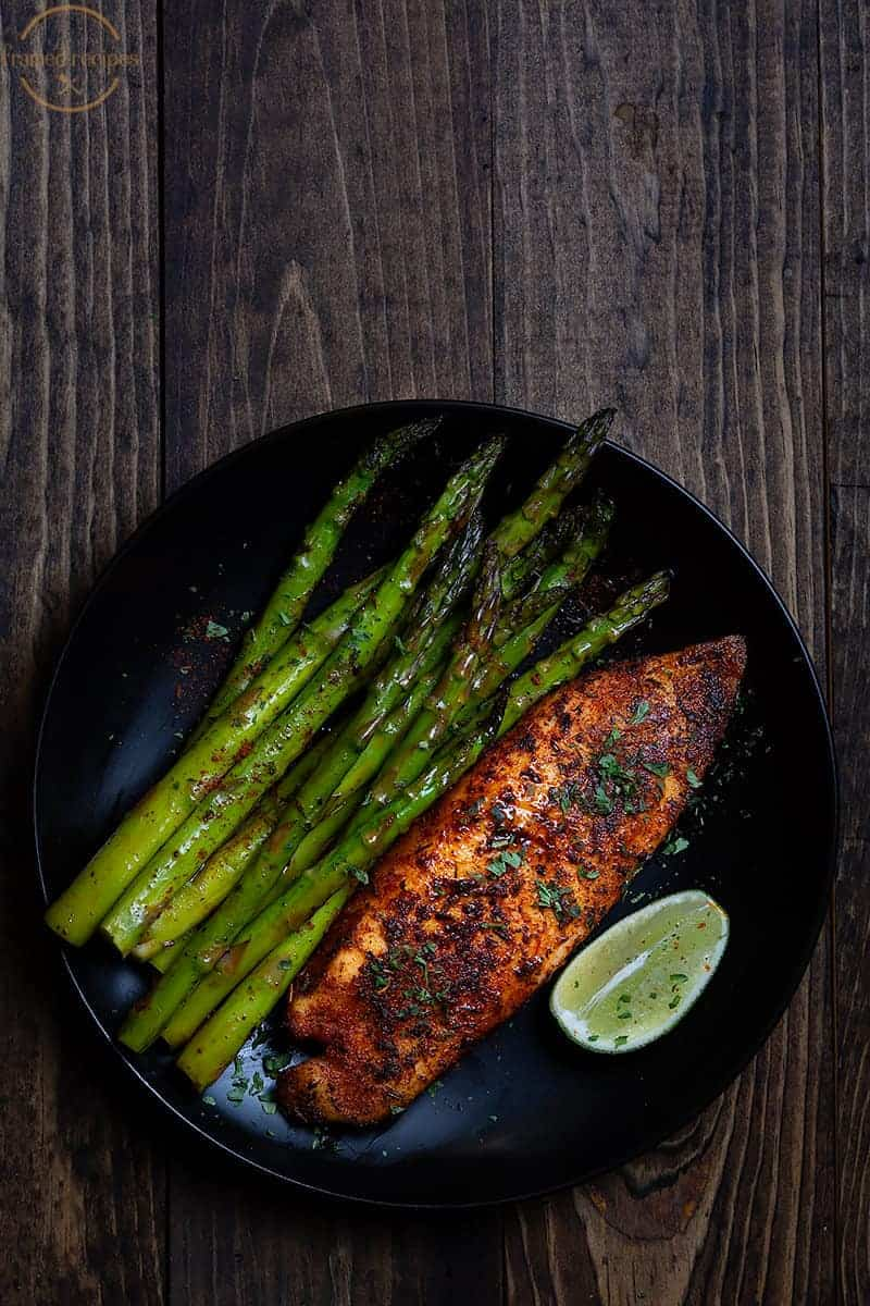 blackened tilapia served with some sautéed asparagus spears.