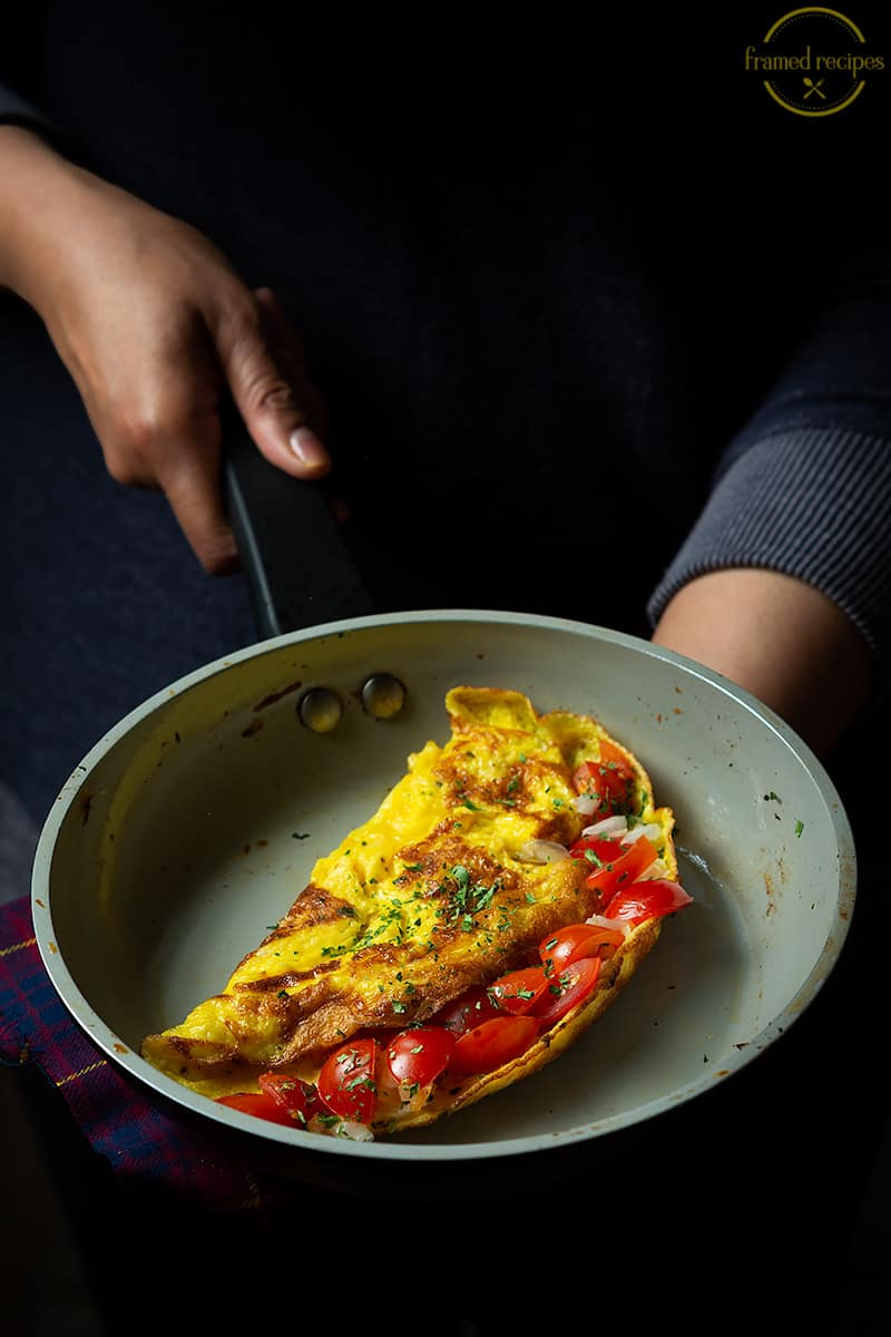 cherry tomatoes filled omelet in a skillet