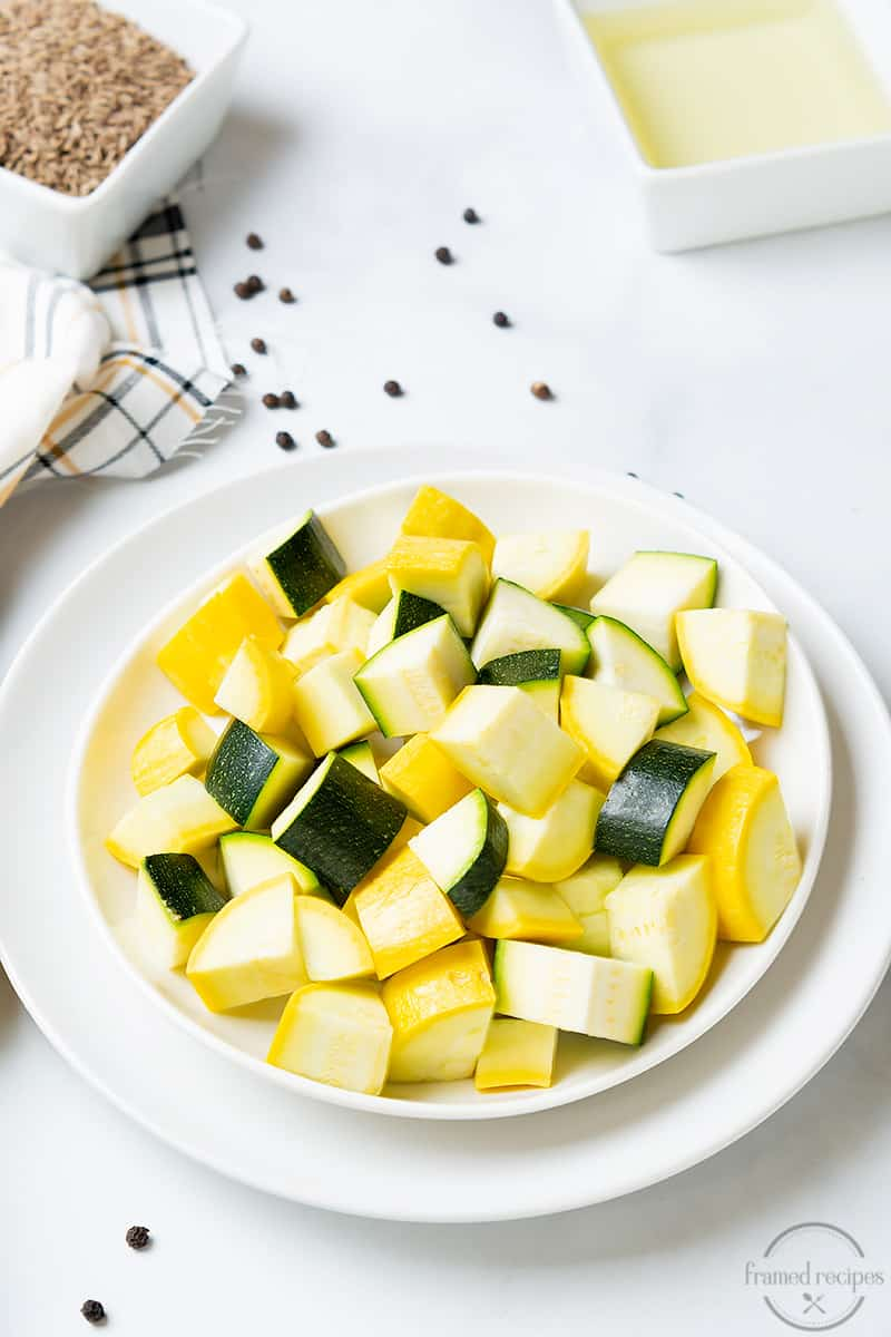 diced yellow aquash and zucchini in a plate along with cumin seeds, black pepper and oil.
