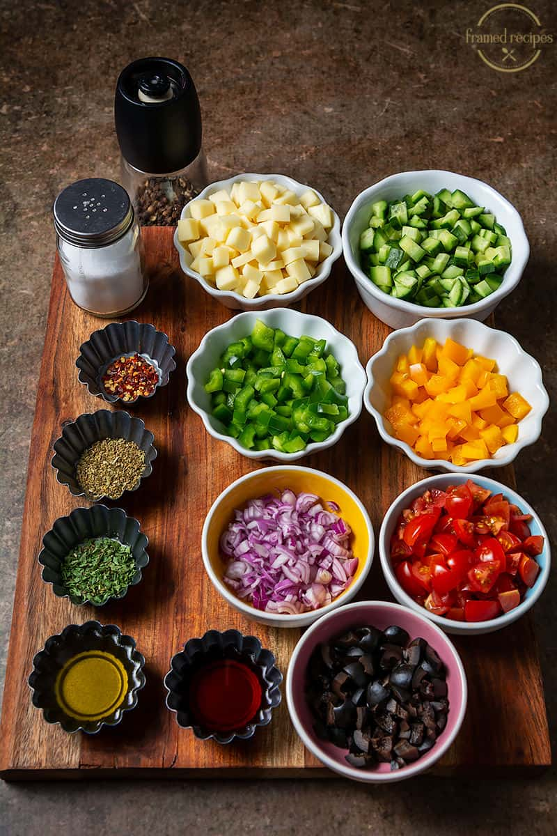 Ingredients for Italian pasta salad - mozzarella cheese, green bell pepper, cucumber, cherry tomatoes, olives, yellow bell pepper, red onion, salt, pepper, red chilli flakes, oregano, basil, parsley, red wine vinegar and olive oil.